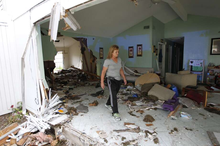 Molly Tatum walks through her best friend's duplex after a vehicle plowed through it and two others early Friday morning in the 12300 block of Sandstone near Cook Road. Photo: Cody Duty, Houston Chronicle