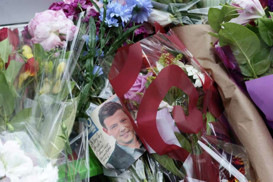 Photographs and flowers are placed at a memorial for Canadian actor Cory Monteith outside the Fairmont Pacific Rim Hotel in Vancouver, B.C., on Tuesday, July 16, 2013. Monteith's body was found in a room at the hotel Saturday. (AP Photo/The Canadian Press, Darryl Dyck) Photo: DARRYL DYCK, SUB / The Canadian Press