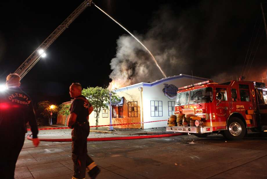 Firefighters mop up after  extinguishing a fire at the historic Oyster House restaurant on the  downtown Olympia waterfront early morning Friday, July 19, 2013.  The fire was reported shortly after midnight at the Oyster House, and  flames shot through the roof and windows. The restaurant back to  1924. The owner says he'll rebuild. (AP Photo/The Olympian, Tony  Overman)