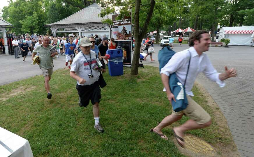 Racing patrons run to secure their places in the picnic area on opening day Friday morning, July 19,