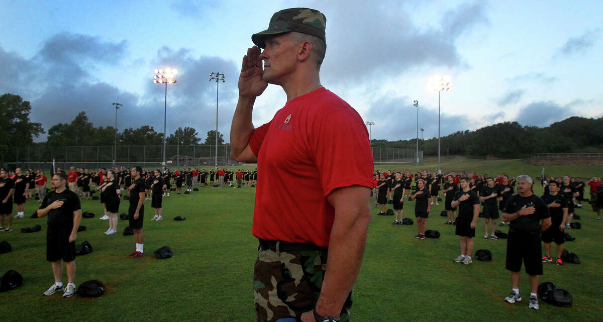 Brian Parks salutes Friday July 19, 2013 at USAA during the insurance giant's Zero Day PT (physical training). About 300 employees took part in the event which intends to provide workers with insight about what military recruits experience during basic training.