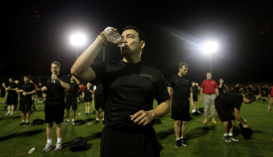 Paul Ybarra hydrates while taking part in USAA's Zero Day PT (physical training) Friday morning July 19, 2013. About 300 employees participated in the event which is intended to provide USAA employees with insight about what military recruits experience in basic training. Photo: JOHN DAVENPORT, SAN ANTONIO EXPRESS-NEWS / ©San Antonio Express-News/Photo may be sold to the public