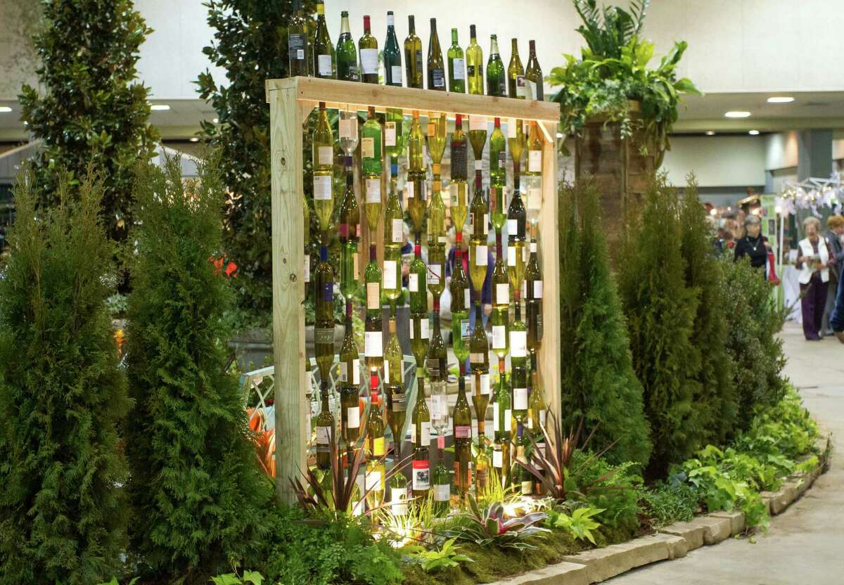 Landscape designer Chris H. Olsen created a decorative wall out of empty wine bottles by threading them onto metal poles inserted into a wooden frame.