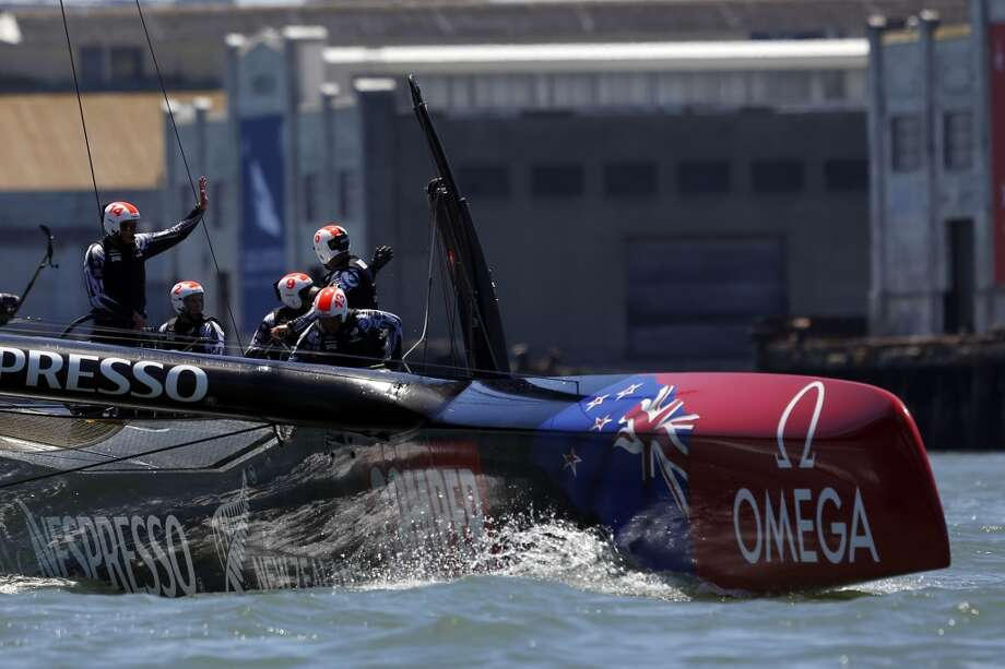 The Emirates Team New Zealand team members wave to fans after winning a point during a solo race against Artemis for the Louis Vuitton Cup in San Francisco, Calif. on July 18, 2013.