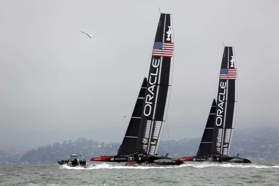 The Oracle Team USA boats sail side by side before a race between the Emirates Team New Zealand and Artemis for a round robin of the Louis Vuitton Cup in San Francisco, Calif. on July 18, 2013.