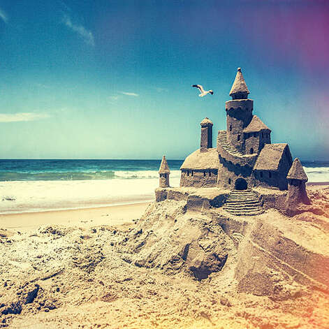 """Mastering the sandcastle The king of the castle—Todd Vander Pluym, winner of nearly 200 sand-sculpting competitions—shares his trade secrets. Test the sand. Squeeze wet sand and roll it back and forth in your hand. If it stays together, it's good sand. If it falls apart, """"you're in the wrong spot—or on the wrong beach,"""" says Vander Pluym. Build a base. Make a circular wall out of dry sand, 6 inches high and 3 feet wide. Add 2 inches of water to circle, then 2 inches of sand. Tamp until water drains. Add dry sand to wall and repeat layering, angling inward to form 18-inch mound. Construct towers. Place a bucket, with the bottom cut out, handle side down on the mound. Alternate layers of sand and water in the bucket, 2 inches at a time, tamping as you go, finishing with water. Perform lift-off. Have one person tap the bucket to release sand right before another one lifts it straight up. Repeat process for more towers, and remove loose sand from around the mound. Add details. Use an offset spatula to square off towers and make stairs; a funnel for roofs; a melon baller for corbels; and a disposable knife for arrow slits—""""a neat little detail that makes a castle look like a castle.""""  Vander Pluym's Redondo Beach–based company, Sand Sculptors International, offers lessons and a how-to DVD, Sandcastles for Everyone; sandsculptors.com More: 14 unsung beach towns   Photo: Thomas J. Story, Sunset.com / © Thomas J. Story/Sunset Publishing"""