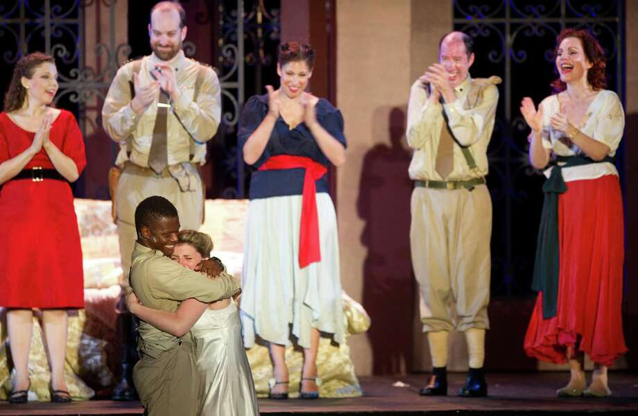 Still in costume from performing in Othello for Curtain Call's Shakespeare on the Green, Kevin Thompson pulls his girlfriend, Julia Maggiola, off the stage after the bow and proposes. Maggiola, who met Thompson when they were both cast in The Tempest during Shakespeare on the Green in 2009, said yes. Photo: Lindsay Perry / Stamford Advocate