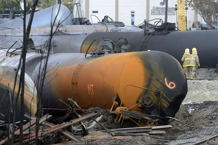 Workers move among damaged tank cars at the crash site of the train derailment and fire Tuesday, July 16, 2013, in Lac-Megantic, Quebec.  The July 6, 2013, derailment that left 37 people confirmed dead and another 13 missing and presumed dead. (AP Photo/Ryan Remiorz, Pool) Photo: Ryan Remiorz, Associated Press