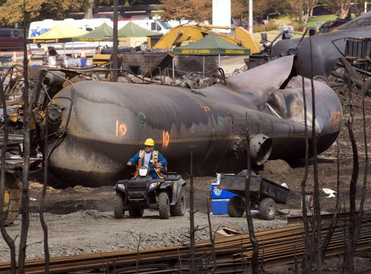 A worker drives past the twisted remains of a tanker car Tuesday, July 16, 2013 in Lac-Megantic, Que