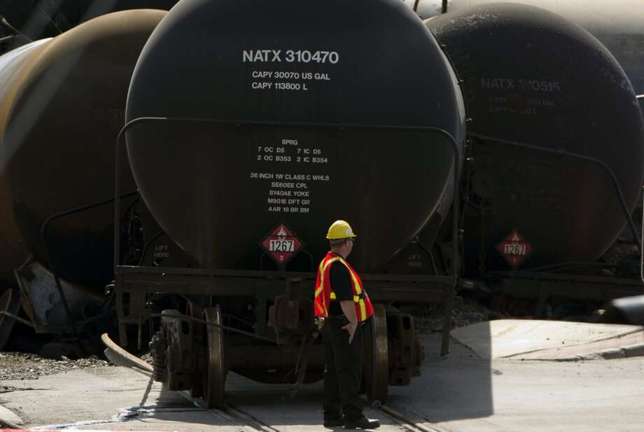 In this Friday, July 12, 2013, photo, work continues at the crash site on in Lac-Megantic, Quebec of a train that derailed igniting tanker cars carrying crude oil that killed fifty people. U.S. and Canadian drillers are producing oil faster than new pipelines can be built. As a result, trains have become an unexpected yet vital way to move this bounty of energy from the continent's midsection to refineries along the coasts. However, since the July 6 tragedy in Lac-Megantic, where a runaway train carrying 72 carloads of crude derailed and killed 50 people, there have been calls for tougher regulations, stronger rail cars and more pipelines.  (AP Photo/The Canadian Press, Ryan Remiorz) Photo: Ryan Remiorz, Associated Press
