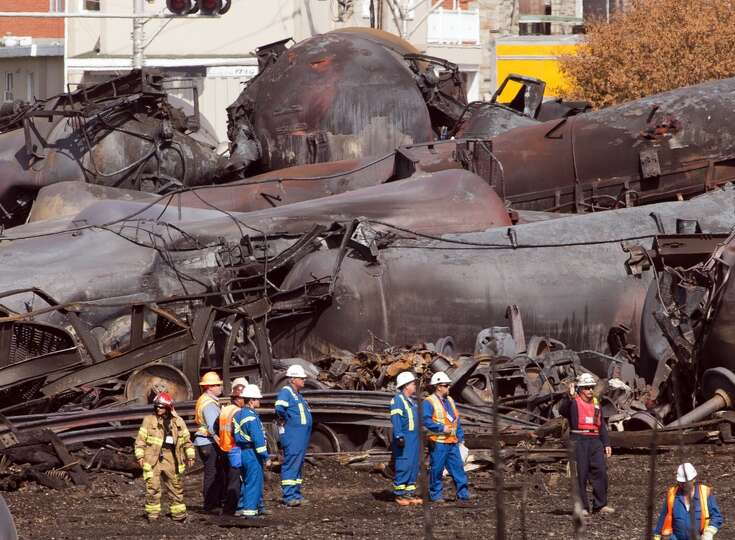 Workers stand before mangled tanker cars Tuesday, July 16, 2013, at the crash site of the train dera