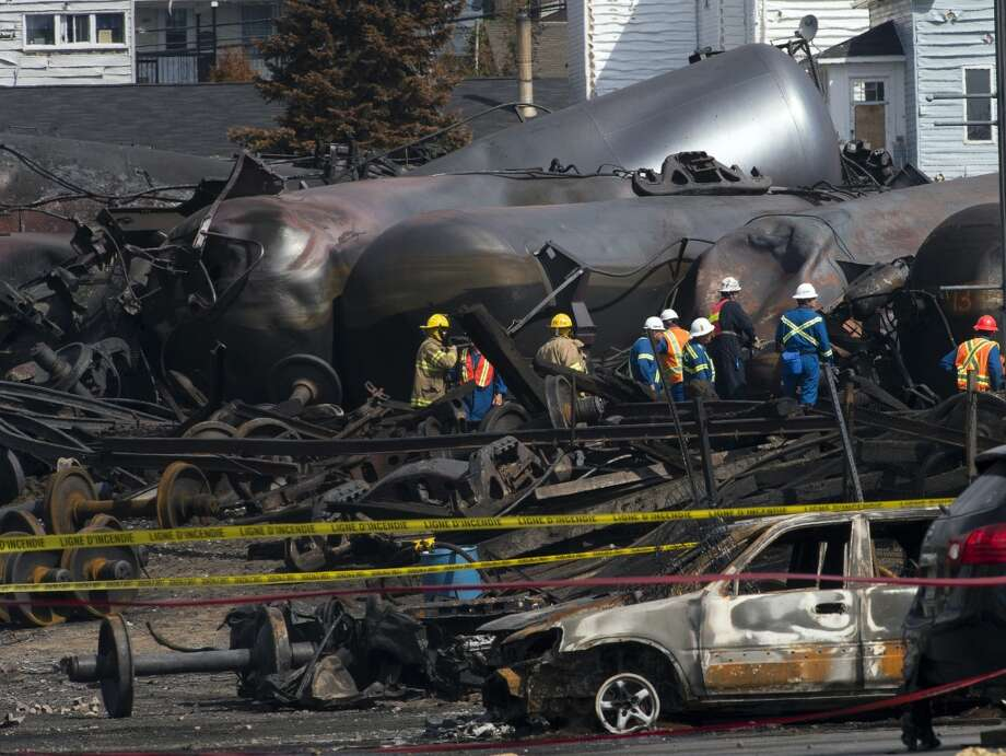 Worker are seen by damaged tanker cars Tuesday, July 16, 2013, as work continues at the crash site of the train derailment and fire in Lac-Megantic, Quebec.  The July 6, 2013 derailment left 37 people confirmed dead and another 13 missing and presumed dead.  (AP Photo/Ryan Remiorz, Pool) Photo: Ryan Remiorz, Associated Press