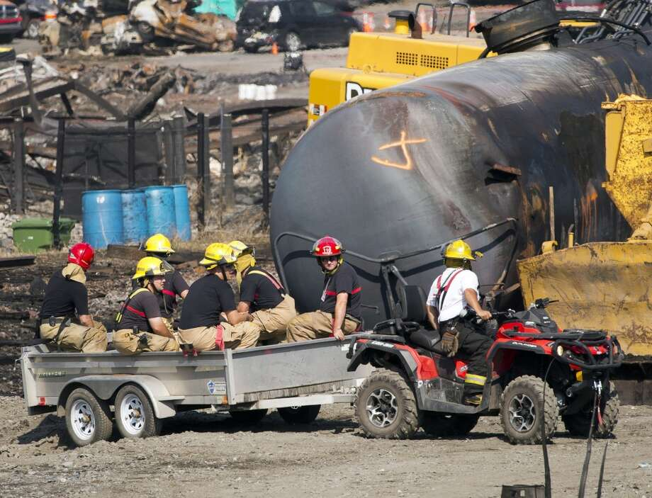 Workers pas tje wreckage of a tanker car  Tuesday, July 16, 2013, at the crash site of the train derailment and fire in Lac-Megantic, Quebec.  The July 6, 2013, accident left 37 people confirmed dead and another 13 missing and presumed dead.  (AP Photo/Ryan Remiorz, pool) Photo: Ryan Remiorz, Associated Press
