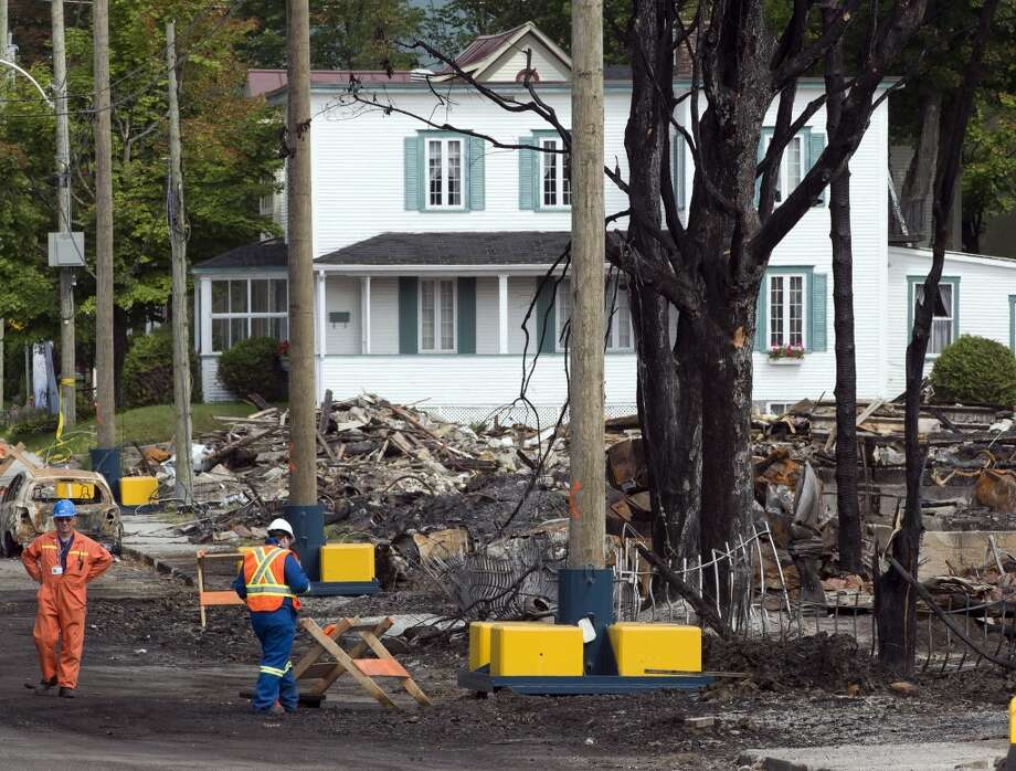 Workers sift through debris Tuesday, July 16, 2013 in Lac-Megantic, Quebec, in front of the white house that  was unscathed by the train derailment July 6, 2013.  The derailment and fire left 37 people confirmed dead and another 13 missing and presumed dead. (AP Photo/ The Canadian Press, Ryan Remiorz) Photo: Ryan Remiorz, Associated Press