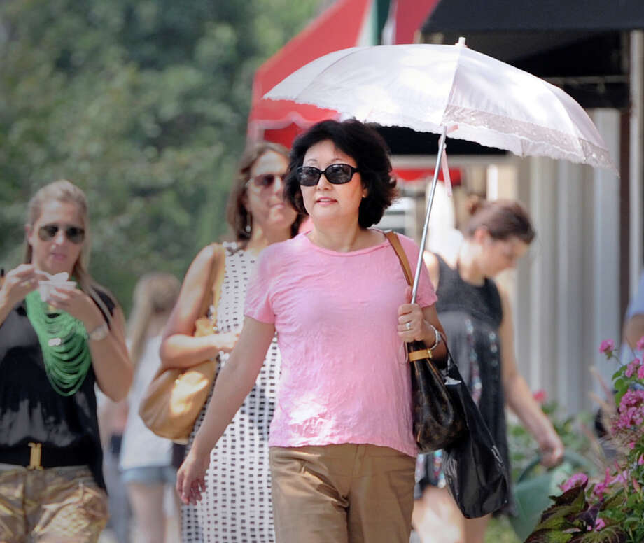 Kyoto Kuro of Greenwich uses a reflective umbrella to stay cool in the 95 degree heat while walking on Greenwich Avenue, Friday afternoon, July 19, 2013. Kuro said this is the first time she has ventured outside during the heat wave and brought her umbrella to avoid getting a sunburn. Photo: Bob Luckey / Greenwich Time