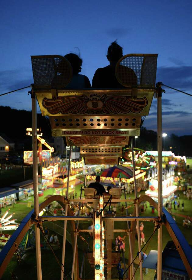 Carnival-goers get a nice view while riding the Ferris wheel at the New Fairfield Lions Club Olde Tyme Carnival in New Fairfield, Conn. on Thursday, July 18, 2013.  The Lions Club's biggest fundraiser of the year, the carnival ran Tuesday through Saturday with games and rides by Stewart Amusement, music from local bands and food cooked by club members. Photo: Tyler Sizemore / The News-Times