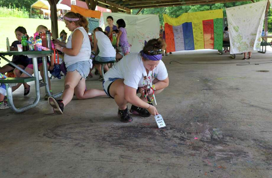Hannah Young, 18, of New Milford, Conn., a staff member at the Clatter Valley Day Camp in New Milford, scrapes dried crayon from the cement floor at the camp Friday, July 19, 2013. Camp staffers spent the morning Friday claening up the damage made by vandals during the previous night. Photo: Carol Kaliff / The News-Times