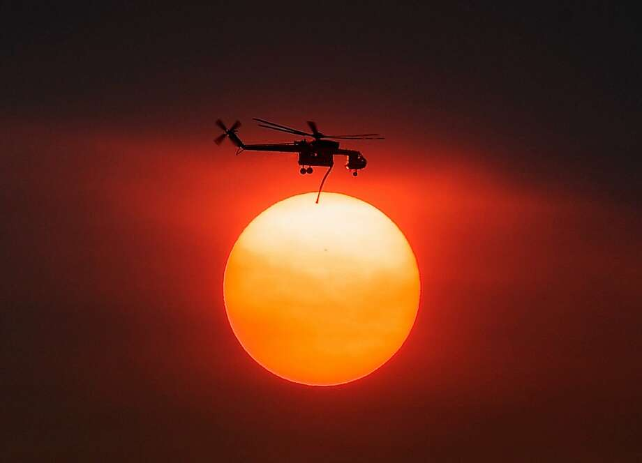 Wet load on the way: Smoke from the Mountain Fire shrouds the sun as a firefighting helicopter heads to the blaze after picking up water from Lake Hemet near Idyllwild, Calif. Photo: Kevork Djansezian, Getty Images