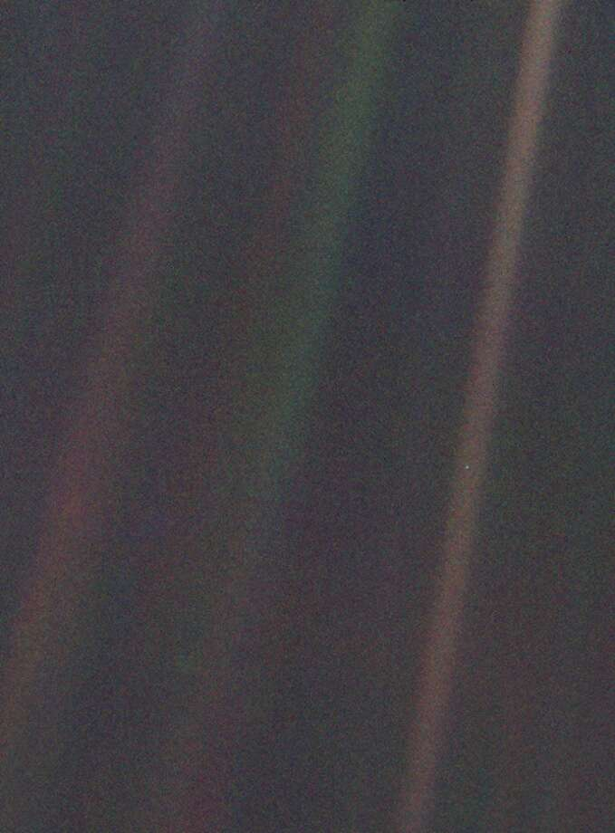 """The famous 'pale blue dot' image taken by Voyager from a distance of 6 billion km from Earth.  """"That's here. That's home. That's us,"""" Carl Sagan wrote."""