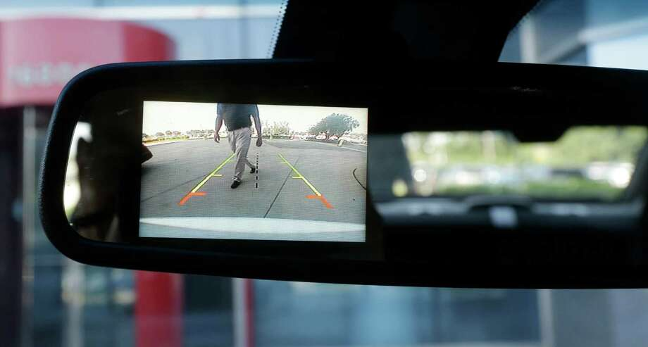 In a photo from July 18, 2013, a new surveillance system that displays on the rear view mirror in police cars automatically sounds a chime, locks the doors and rolls up the windows if it detects someone approaching the car from behind. It was developed by Ford  engineer Randy Freiburger who works with police and ambulance customers to make sure the company's vehicles are meeting their needs. Photo: Carlos Osorio