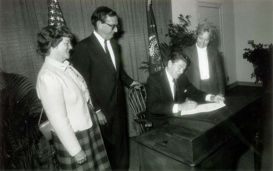 In Fairfield Town Hall, Oct. 26th, 1984, President Ronald Reagan signs a bill into law designating islands off of Norwalk, Milford Point and Guilford as wildlife refuges. He is joined here by Rep. Stewart McKinney and his wife Lucie, left, and Rep. Nancy Johnson. Photo: File Photo / Connecticut Post File Photo