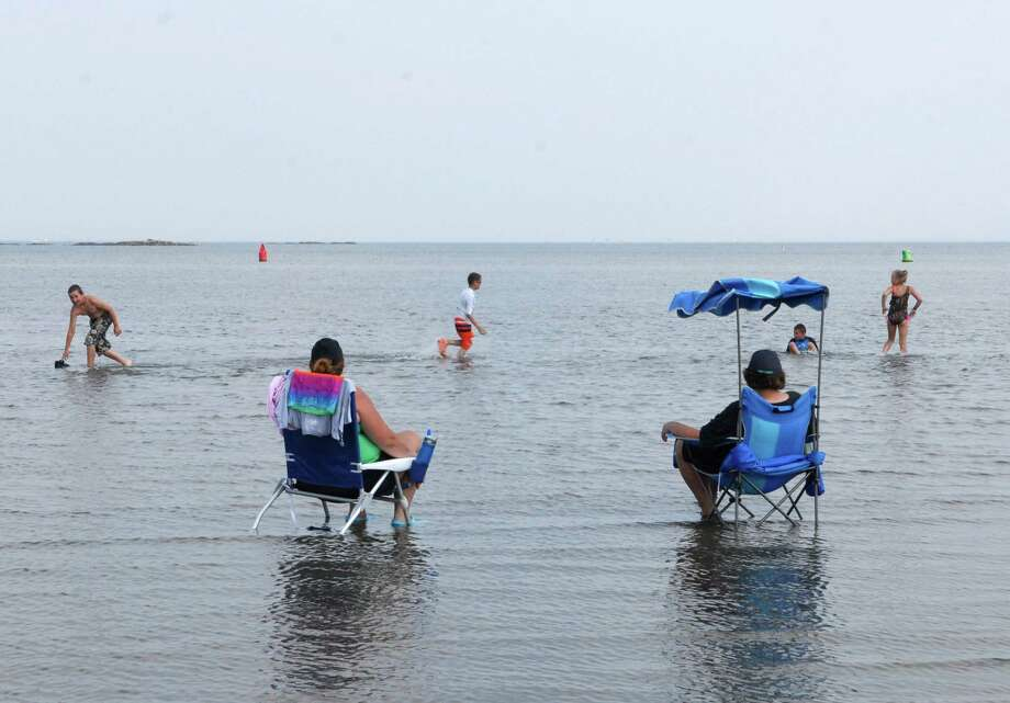 Kimberly Benkwitt and Julia Coos cool off sitting in the water at low tide and watching their children play at West beach in Stamford, Conn. on Friday July 19, 2013. Photo: Dru Nadler / Stamford Advocate Freelance