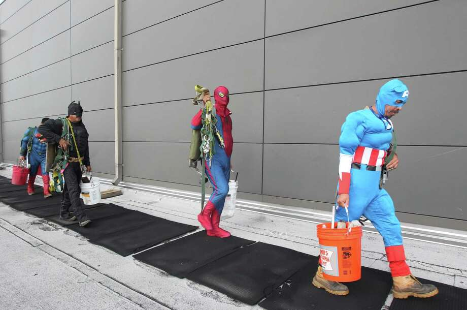 "Mario Orellana as ""Batman, Gerber Abarca as ""Spiderman"", and Juan Torres as ""Captain America"" get ready to start scaling the hospital exteriors to wash windows and surprise patients at Texas Children's Hospital on Friday, July 19, 2013, in Houston. Photo: Mayra Beltran / © 2013 Houston Chronicle"