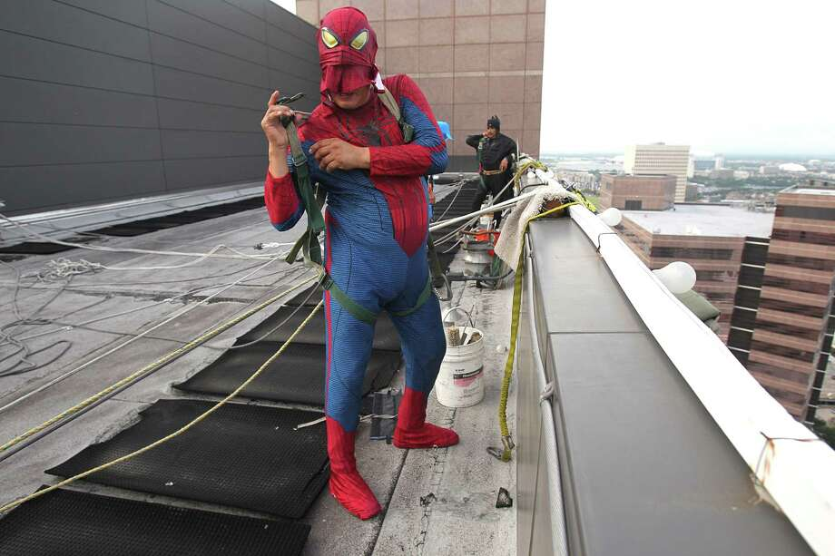"Gerber Abarca as ""Spiderman"" straps on holsters to safely begin to scale the hospital exteriors to wash windows and surprise patients at Texas Children's Hospital on Friday, July 19, 2013, in Houston. Photo: Mayra Beltran / © 2013 Houston Chronicle"