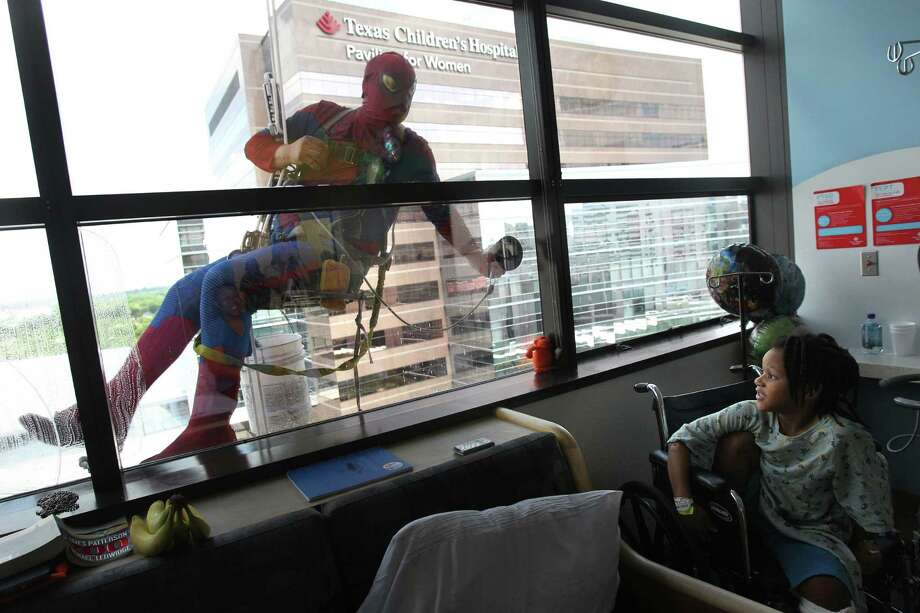"Gerber Abarca as ""Spiderman"" surprises patient Turner Robinson, 6, as super heroes start scaling the hospital exteriors to wash windows at Texas Children's Hospital on Friday, July 19, 2013, in Houston. Photo: Mayra Beltran / © 2013 Houston Chronicle"