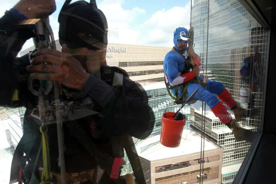 "Mario Orellana as ""Batman"" and Juan Torres as ""Captain America"" look to view patients during a surprise visit as they scale the hospital exteriors to wash windows at Texas Children's Hospital on Friday, July 19, 2013, in Houston. Photo: Mayra Beltran / © 2013 Houston Chronicle"