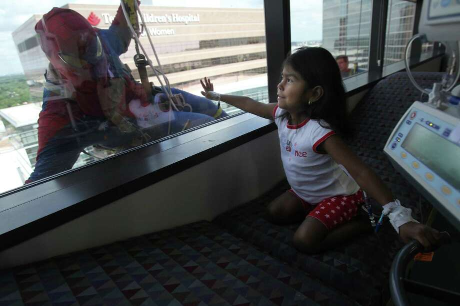 "Nadia Munoz, 5, views super hero Gerber Abarca as ""Spiderman"" who is surprising patients by scaling the hospital exteriors to wash windows at Texas Children's Hospital on Friday, July 19, 2013, in Houston. Photo: Mayra Beltran / © 2013 Houston Chronicle"
