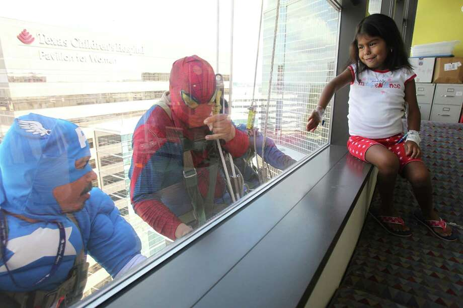 "Nadia Munoz, 5, views Juan Torres as ""Captain America"" and Gerber Abarca as ""Spiderman"" who are surprising patients by scaling the hospital exteriors to wash windows at Texas Children's Hospital on Friday, July 19, 2013, in Houston. Photo: Mayra Beltran / © 2013 Houston Chronicle"