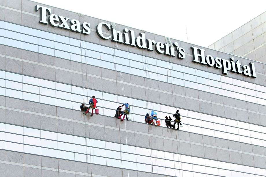 Superman, Spiderman, Batman, and Captain America surprise patients by scaling the hospital exteriors and washing windows at Texas Children's Hospital on Friday, July 19, 2013, in Houston. Photo: Mayra Beltran / © 2013 Houston Chronicle