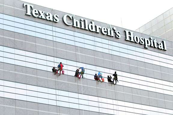 Superman, Spiderman, Batman, and Captain America surprise patients by scaling the hospital exteriors and washing windows at Texas Children's Hospital on Friday, July 19, 2013, in Houston.