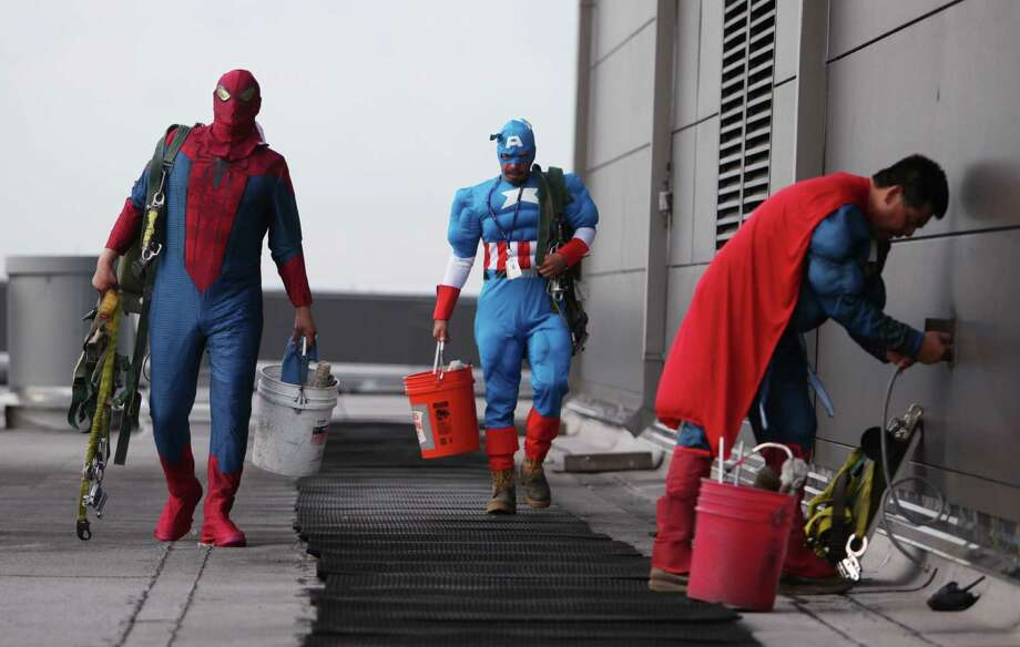 "Gerber Abarca as ""Spiderman"", Juan Torres as ""Captain America"" and Ismael Rivera as ""Superman"" get ready to start scaling the hospital exteriors to wash windows and surprise patients at Texas Children's Hospital on Friday, July 19, 2013, in Houston. Photo: Mayra Beltran / © 2013 Houston Chronicle"