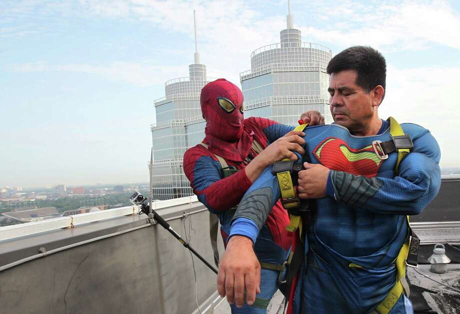 "Gerber Abarca as ""Spiderman"", assists Ismael Rivera as ""Superman"" to start on safety gear and begin scaling the hospital exteriors to wash windows and surprise patients at Texas Children's Hospital on Friday, July 19, 2013, in Houston. Photo: Mayra Beltran / © 2013 Houston Chronicle"