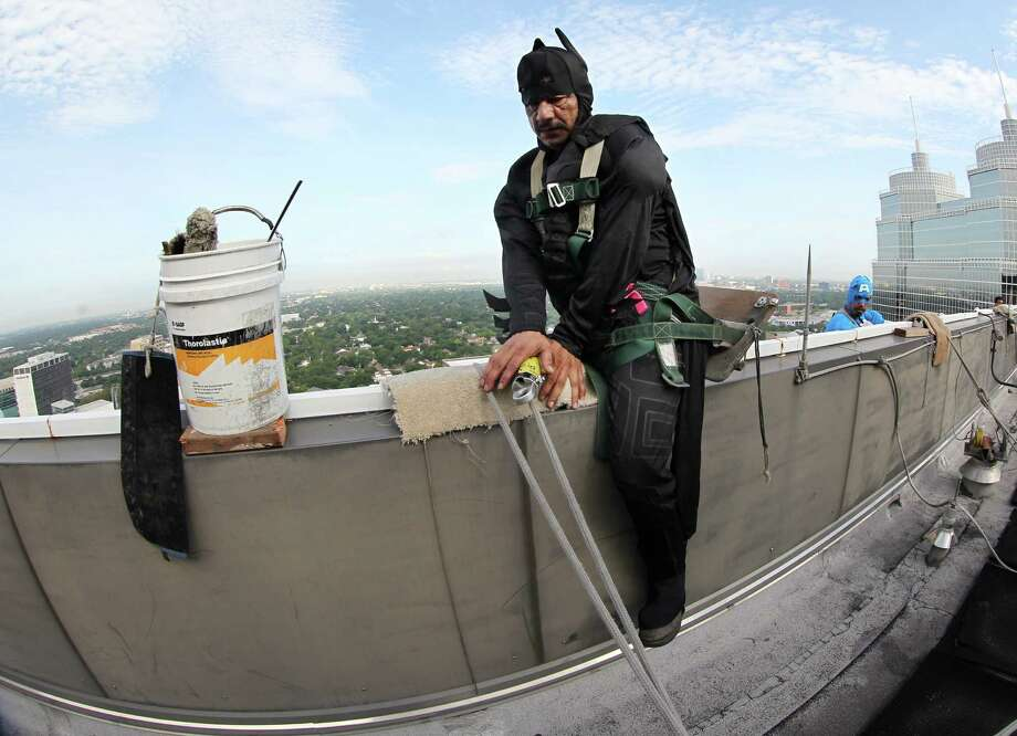"Mario Orellana as ""Batman sits on the edge of the building as he safely makes his way over the wall to begin scaling the hospital exteriors to wash windows and surprise patients at Texas Children's Hospital on Friday, July 19, 2013, in Houston. Photo: Mayra Beltran / © 2013 Houston Chronicle"