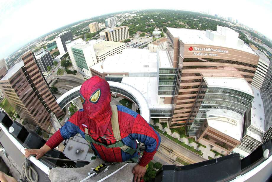 "Gerber Abarca as ""Spiderman"" dangles off the building to begin scaling the hospital exteriors to wash windows and surprise patients at Texas Children's Hospital on Friday, July 19, 2013, in Houston. Photo: Mayra Beltran / © 2013 Houston Chronicle"