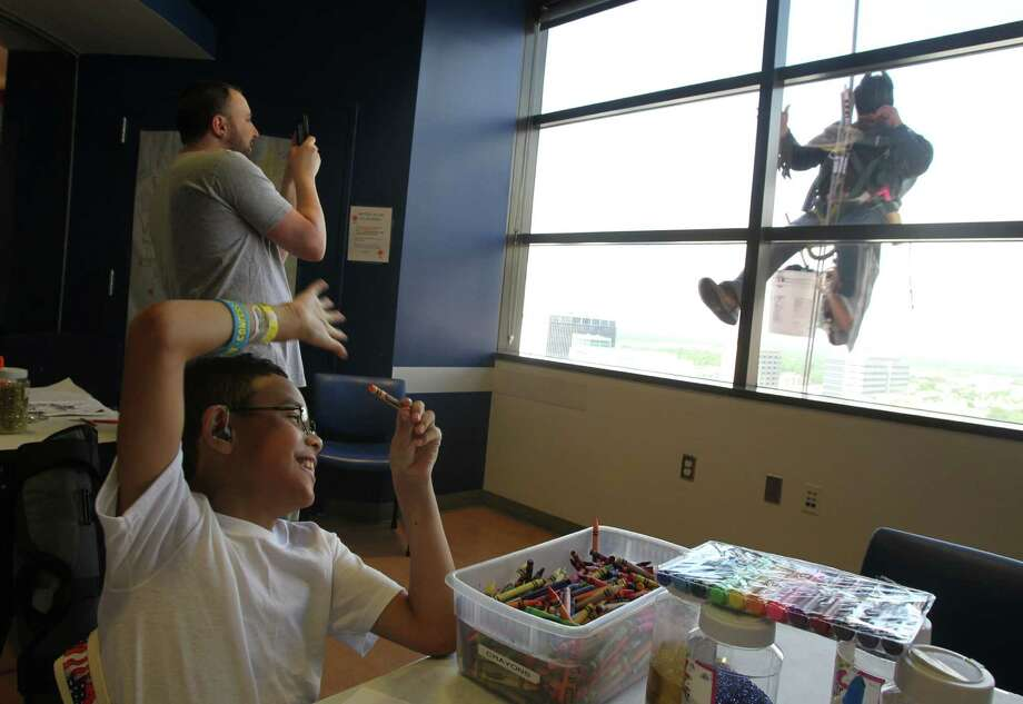 "Mario Orellana as ""Batman"" drops into an activity room as patient Mikael Allgoodbrisco, 8, waves super heroes surprising patients by scaling the hospital exteriors to wash windows at Texas Children's Hospital on Friday, July 19, 2013, in Houston. Photo: Mayra Beltran / © 2013 Houston Chronicle"