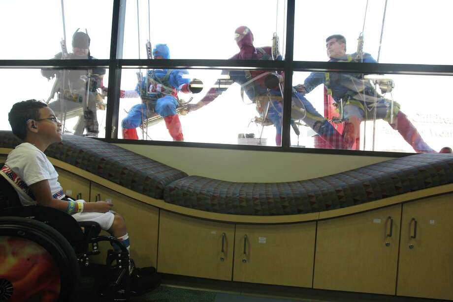 "Mario Orellana as ""Batman"", Juan Torres as ""Captain America"", Gerber Abarca as ""Spiderman"", and Ismael Rivera as ""Superman"" drop into an activity room as patient Mikael Allgoodbrisco, 8, smiles back to super heroes surprising patients by scaling the hospital exteriors to wash windows at Texas Children's Hospital on Friday, July 19, 2013, in Houston. Photo: Mayra Beltran / © 2013 Houston Chronicle"