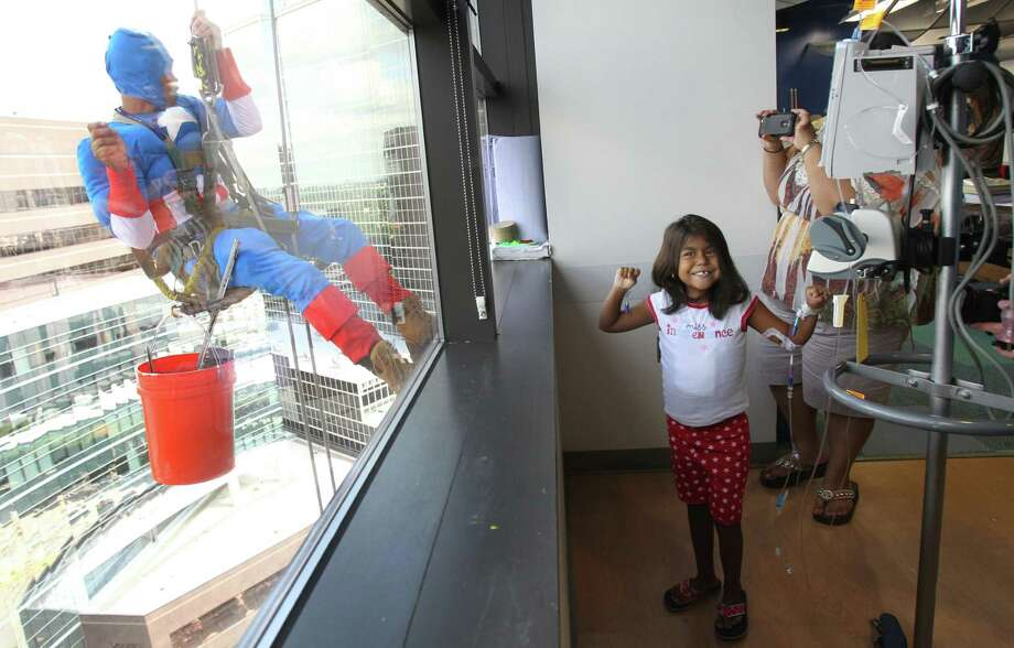 "Nadia Munoz, 5, at Juan Torres as ""Captain America"", who is her favorite super hero while they surprise patients by scaling the hospital exteriors to wash windows at Texas Children's Hospital on Friday, July 19, 2013, in Houston. Photo: Mayra Beltran / © 2013 Houston Chronicle"