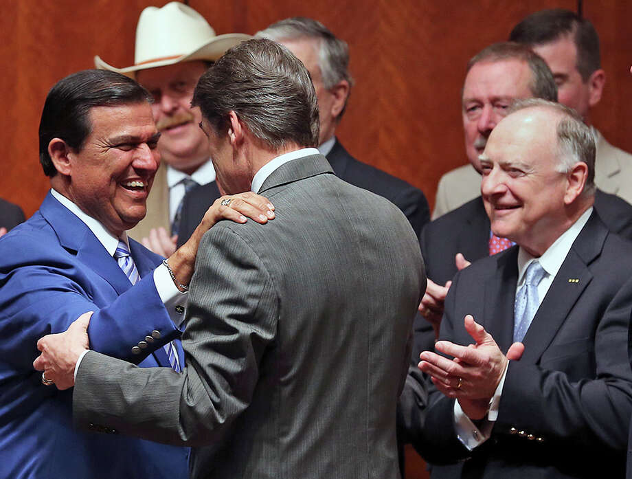 Again wearing his blue coat, Senator Eddie Lucio D-Brownsville, greets Governor Rick Perry before the signing into law of the abortions restrictions bill  on July 18, 2013. Photo: TOM REEL, San Antonio Express-News / San Antonio Express-News