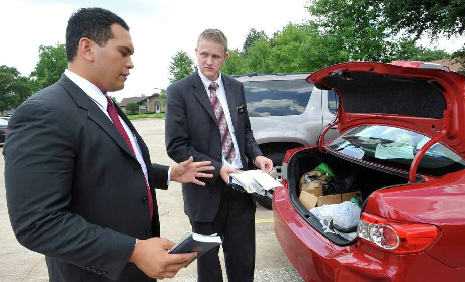 Elder Beaver Ho Ching, left, talks about some of the content in the pamphlets they hand out going door-to-door as Elder Joshua Limb, right, pulls more from their trunk.  Officials with the Church of Jesus Christ of Latter Day Saints, (Mormons), recently announced they would extend missionary service to the Internet and other mobile platforms to reach out to more people, possibly ending, or cutting down the amount of time spent on the practice of door-to-door missionary work in the future.  Dave Ryan/The Enterprise Photo: Dave Ryan