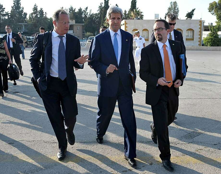 U.S. Secretary of State John Kerry (center) says Israel and the Palestinians have reached an agreement on a basis for resuming peace negotiations. He expects initial talks in a week or so. Photo: Mandel Ngan, Associated Press