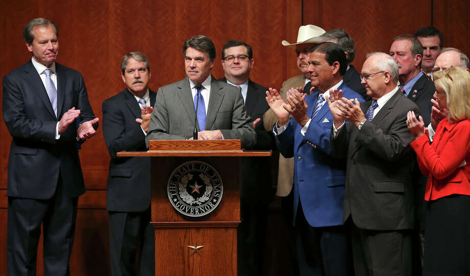 Lawmakers, including Lt. Governor David Dewhurst and State Sen. Ediie Lucio D-Brownsville (blue coat) applaud as Governor Rick Perry speaks before he signs into law the abortions restrictions bill  on July 18, 2013. Photo: TOM REEL