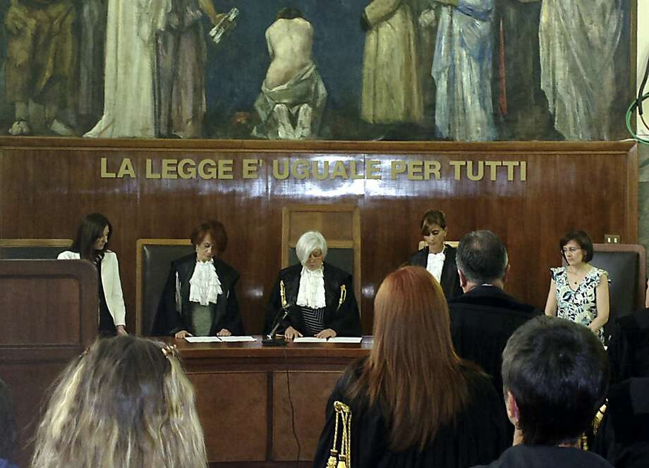 "In this photo taken with a cellular phone, judge Anna Maria Gatto, center, reads the sentence at the Milan court, Italy, Friday, July 19, 2013. A Milan court on Friday, July 19, 2013 convicted three of ex-premier Silvio Berlusconi's former aides of procuring prostitutes for the media mogul's infamous ""bunga bunga"" parties. The court also handed down stiff prison terms: seven years to Emilio Fede, a longtime executive in the mogul's TV networks; seven years to Dario ""Lele"" Mora, a talent agent, and five years to Nicole Minetti, a former regional politician who professed love for the ex-premier. Berlusconi wasn't on trial in this case, but he was convicted separately last month of paying for sex with a minor and trying to cover it up. Both he and the young woman, a Moroccan who goes by her stage name ""Ruby,"" had denied having sex. (AP Photo/Antonio Calanni) Photo: Antonio Calanni, Associated Press"