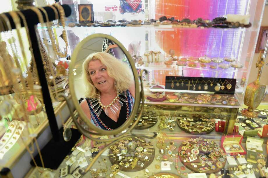 Dawn Sheppard, owner of Dawn's Vintage Jewelry Store in Brookfield, is seen through the reflection of a vintage mirror in her store on Friday, July 19, 2013.  The store, which features thousands of pieces of jewelry and a large collection of antiques and collectibles, recently celebrated its five-year anniversary. Photo: Tyler Sizemore / The News-Times