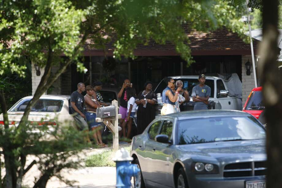 Onlookers watch as police investigate a scene where individuals were held captive. Photo: Cody Duty, Houston Chronicle