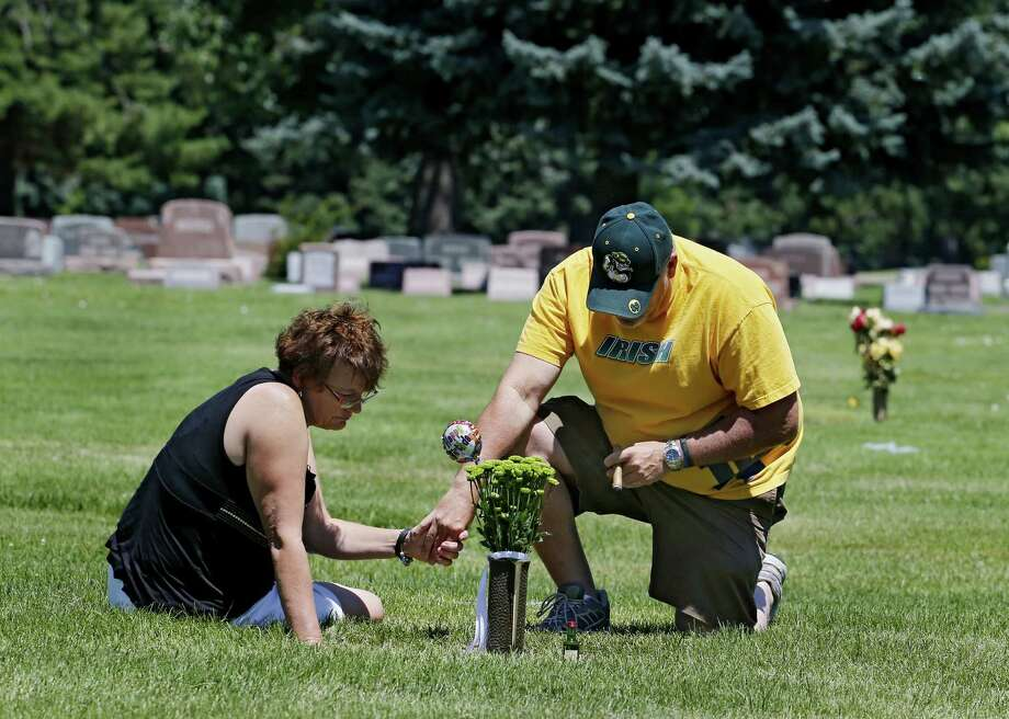 Tom Sullivan and his wife Terry hold hands as they visit the grave site of their son Alex Sullivan on Thursday, July 18, 2013,  in Wheat Ridge, Colo. Alex was killed along with 11 others in the Aurora theater shooting last July on his 27th birthday.  Saturday is the anniversary of the shooting. Photo: Ed Andrieski