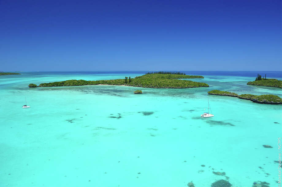 New Caledonia:Gadji Bay, Isle of Pines. This South Pacific oasis is marked by green trees, blue waters and little development.